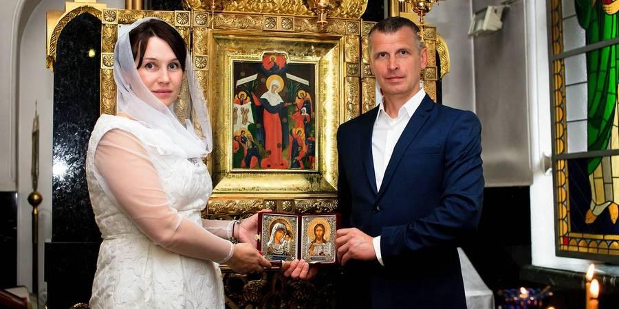 В конце мужчину и женщину благословляют иконами